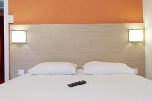 A bed or beds in a room at Premiere Classe Poitiers Futuroscope - Chasseneuil