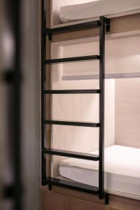 A bunk bed or bunk beds in a room at Quarters Capsule Hostel