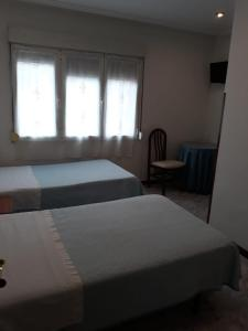 A bed or beds in a room at Hostal González