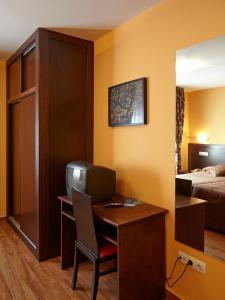 Una televisión o centro de entretenimiento en Hotel Rico