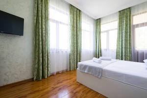 A bed or beds in a room at Sunny Hotel Batumi