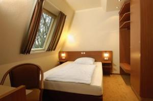 A bed or beds in a room at Hotel Falk