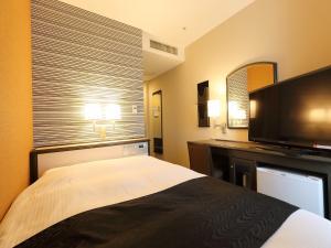 A bed or beds in a room at APA Hotel Takaoka-Marunouchi