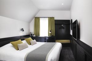A bed or beds in a room at Hôtel Du Dragon
