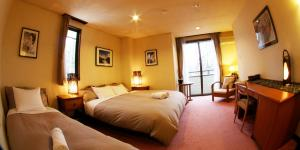 A bed or beds in a room at Morino Lodge - Hakuba