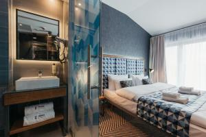 A bed or beds in a room at Avena Boutique Hotel by Artery Hotels