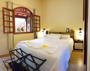 A bed or beds in a room at Pousada Kafundó - Inhotim
