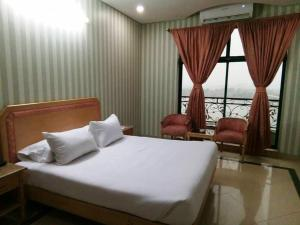 A bed or beds in a room at Tulip Riverside Hotel