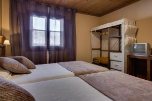 A bed or beds in a room at Aldea Rural A Cortiña