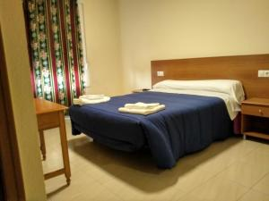 A bed or beds in a room at Hostal Orly
