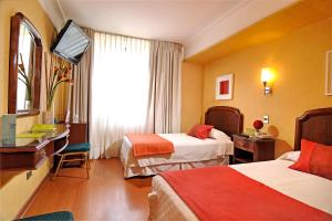 A bed or beds in a room at Hotel Gran Palace
