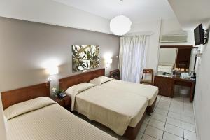 A bed or beds in a room at Epidavros Hotel