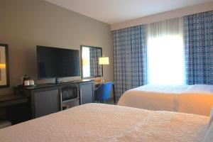 A bed or beds in a room at Hampton Inn West Plains