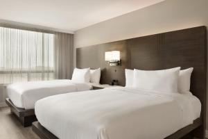 A bed or beds in a room at Embassy Suites By Hilton Montreal Airport
