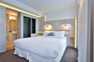A bed or beds in a room at Hôtel Le Marcel Paris Gare de l'Est