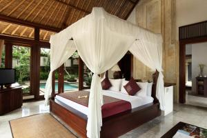A bed or beds in a room at The Ubud Village Resort & Spa