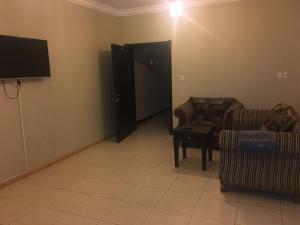 Uma TV ou centro de entretenimento em Al Qimah Apartments
