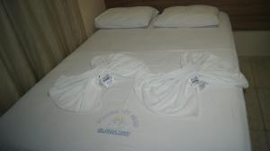 A bed or beds in a room at Hotel Pousada dos Anjos