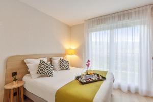 Кровать или кровати в номере Zenitude Hôtel-Résidences Divonne Confort