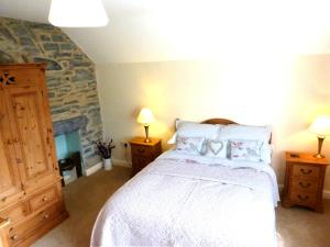 A bed or beds in a room at Dolmurgoch Snowdonia Cottage