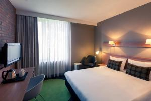 A bed or beds in a room at Mercure Hotel Zwolle