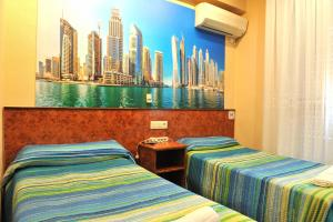 A bed or beds in a room at Hostal Venecia