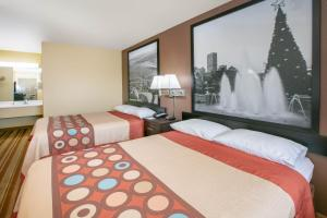 A bed or beds in a room at Super 8 by Wyndham Big Cabin/Vinita Area
