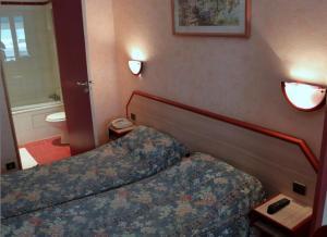 A bed or beds in a room at Hôtel Aladin