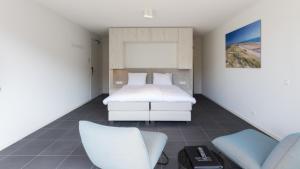 Een bed of bedden in een kamer bij Duinhotel Tien Torens - Seayou Zeeland