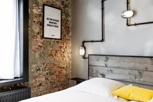 A bed or beds in a room at Upstairs Hotel