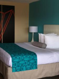 A bed or beds in a room at Howard Johnson by Wyndham Airport Florida Mall
