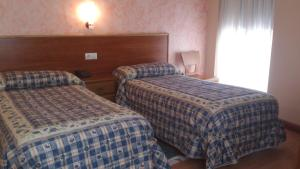 A bed or beds in a room at Hostal Restaurante Boccalino