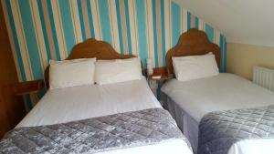 A bed or beds in a room at Fiddlestone Bar and B&B