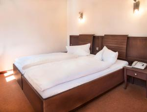 A bed or beds in a room at Hotel Alte Canzley