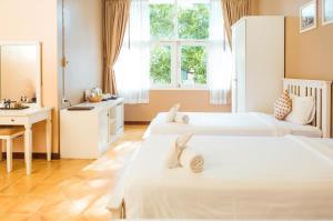 Кровать или кровати в номере Feung Nakorn Balcony Rooms and Cafe