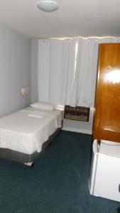 A bed or beds in a room at San Martin Hotel