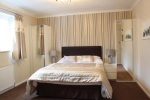 A bed or beds in a room at Abbey Grange Hotel