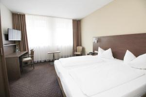 A bed or beds in a room at Hotel Berliner Ring