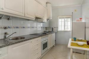 A kitchen or kitchenette at FLH Muralhas da Vila Apartment