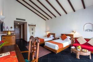 A bed or beds in a room at Shangri-La Village Resort, Pokhara