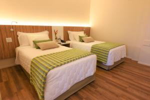 A bed or beds in a room at Quality Hotel Aracaju