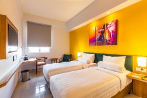 A bed or beds in a room at Great Diponegoro Hotel Surabaya