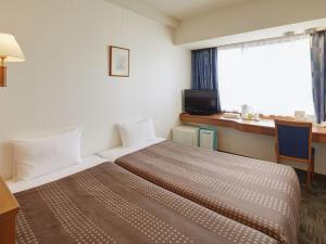 A bed or beds in a room at Hotel Roco Inn Okinawa