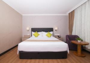 A bed or beds in a room at Kravan Hotel