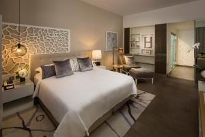 سرير أو أسرّة في غرفة في Beach Rotana Residences