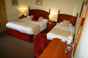 A bed or beds in a room at Queens Head Inn