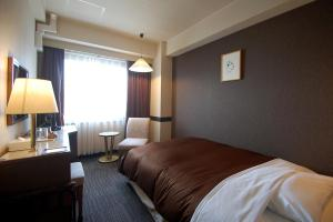 A bed or beds in a room at Hotel Excel Okayama