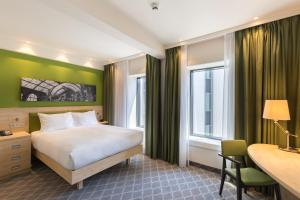 A bed or beds in a room at Hampton By Hilton Antwerp Central Station