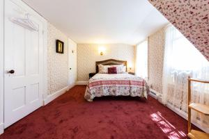 A bed or beds in a room at The Elmhurst Inn