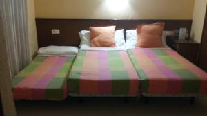 A bed or beds in a room at Hostal Les Collades